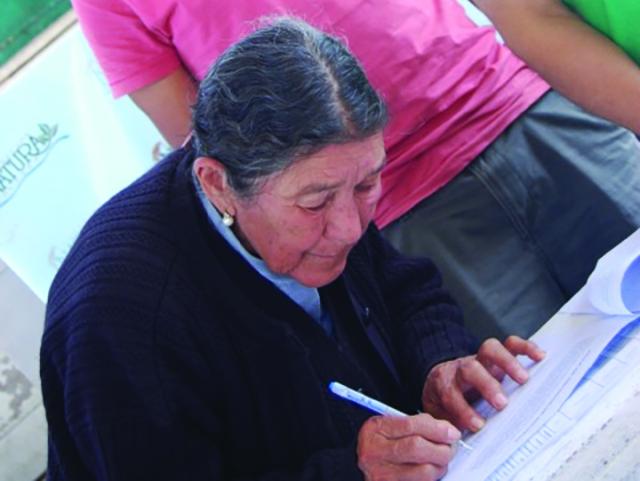 Francisca Villalba de Perez signing conservation agreement – Natura Bolivia'